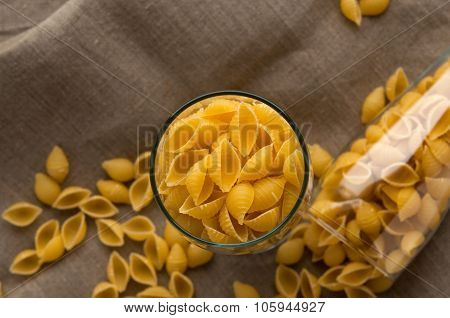 Art still life shell macaroni pasta in glass on hessian linen fabric cloth background