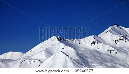Panoramic View On Snowy Winter Mountains And Clear Blue Sky In Sun Day