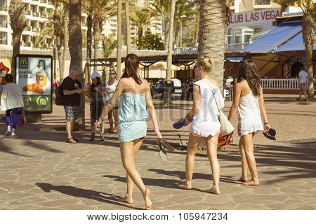 Three Young Girls Walk Along The Promenade. Playa De Las Americas, Tenerife, Canary Islands, Spain