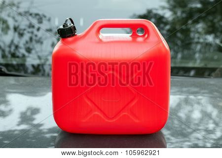 New Red Plastic Jerrycan Stands On Car Hood