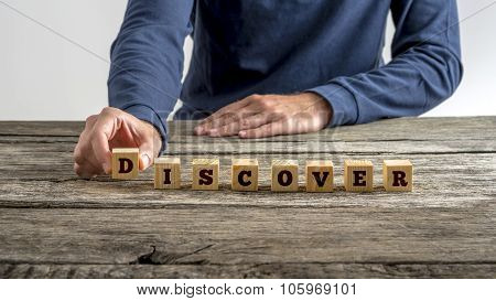 Front View Of A Man Assembling Word Discover With Wooden Cubes