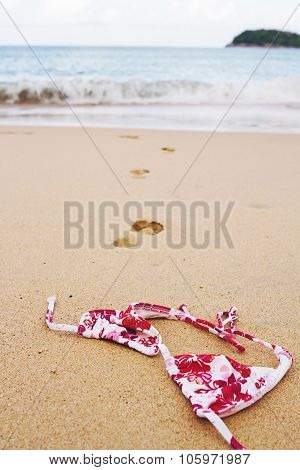Bikini Top Lying On Beach With Footprints Into Surf