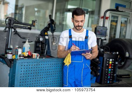 Male mechanic writing on clipboard in  repair shop