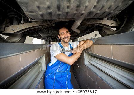 smiling mechanic underneath a car