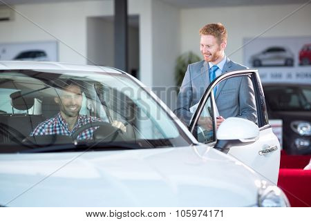 car dealer showing new car to customer