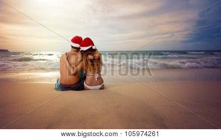 Embracing couple on beach looking sunset with Christmas hat