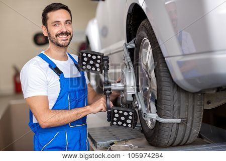 smiling   serviceman checking wheel alignment in a car workshop