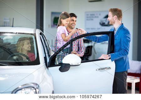 Sales manager at a showroom car with  young family as buyers