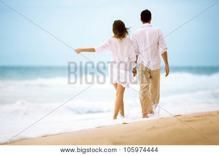 back view of happy romantic young couple walking at the beach
