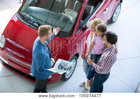 Young family with car agent in  the car dealership  saloon