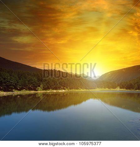 sunrise over lake and mountains