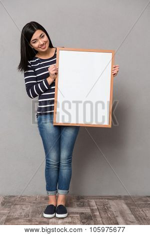 Beautiful happy smiling asian girl in striped jumper looking at camera holding white frame