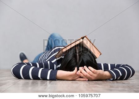 Young woman in striped jumper sleeping on the floor with book on her face