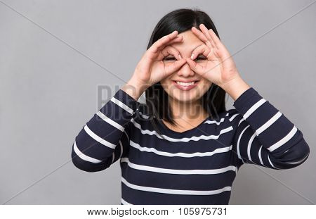 Young beautiful happy smiling woman in striped jumper looking at camera making hands like a mask on her face