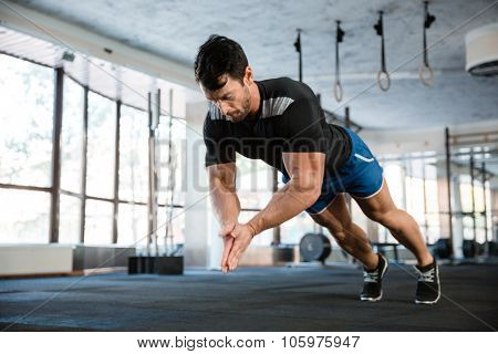 Sportsman wearing blue shorts and black t-shirt doing push-up with claping