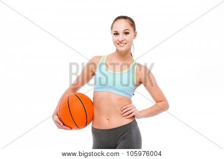Young happy smiling beautiful sportswoman in blue top and grey leggins holding basketball ball
