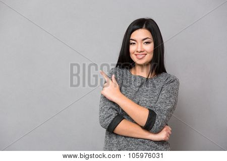 Portrait of a happy woman pointing finger away and looking at camera over gray background