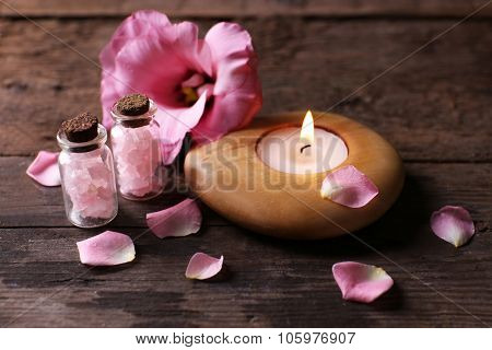 Tenderness composition of alight candle with flower petals on wooden background
