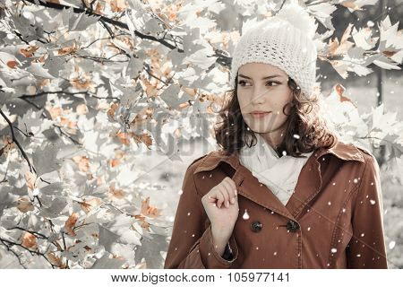 Portrait of a young beautiful woman with falling snow