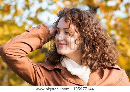 Beautiful young woman with curly hair posing in the front of blurred yellow leaves