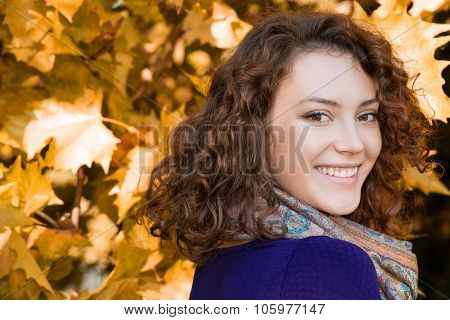 Close-up portrait of a beautiful young woman with curly hair posing in the front of yellow leaves