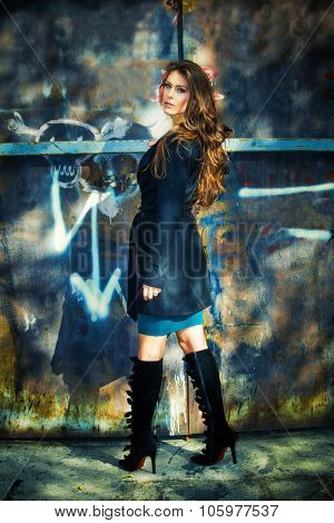 beautiful long hair young woman portrait in coat and high heels black boots in front old rusty metal doors, full body shot