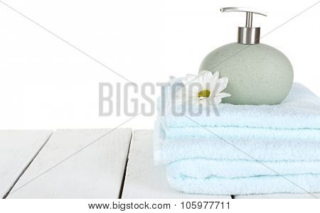 Soft towels with dispenser and flower isolated on white