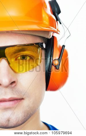 Close-up face portrait of young builder worker in protective hardhat with ear muff and protective glasses