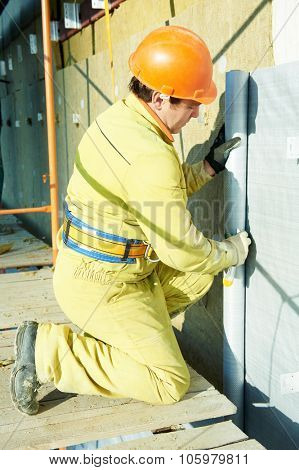 facade plasterer builder at outdoor building external wall insulation with wind protection film