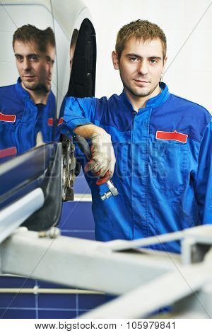 car mechanic portrait during examining car wheel brake disc and shoes of lifted automobile at repair service station