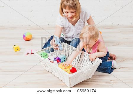 Baby girl and her older sister play with toys