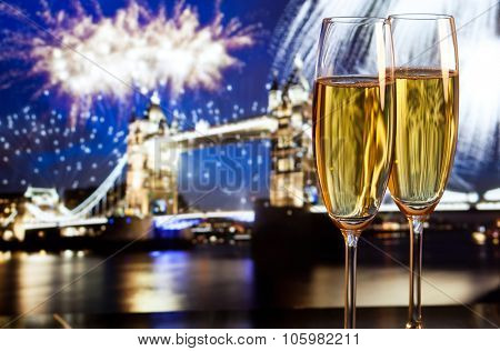 Toasting with champagne in London - Tower bridge with fireworks in the background