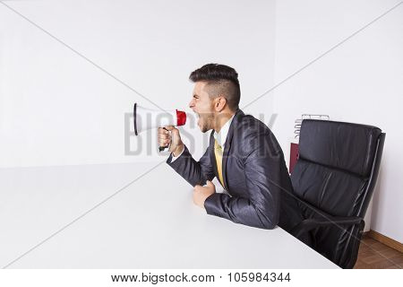 Handsome businessman at his office screaming over the megaphone
