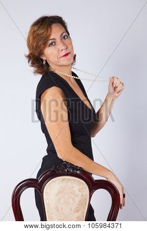 Mature woman next to an old chair