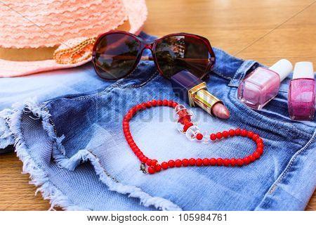 Summer women's accessories: sunglasses red, beads, denim shorts, sun hat, nail polish, lipstick open