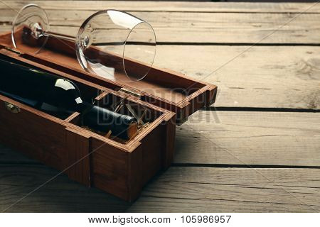 Bottle of wine and empty glass in case on wooden table