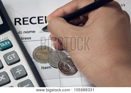 Hand Someone Is Writing Name On Document.coin And Calculator On Receipt Document.