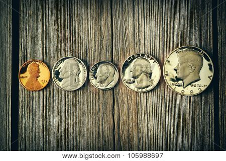 Five US cent coins over wooden background