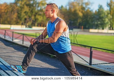 Athletic Man Trains, Stretched On Bench  Stadium. Concept Of Health And Strength