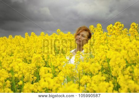 Young Happy Woman Is Walking In Canola Field Under Storm Clouds