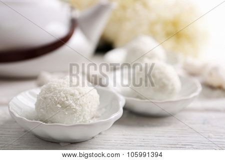 Homemade coco sweets on plate, on light background