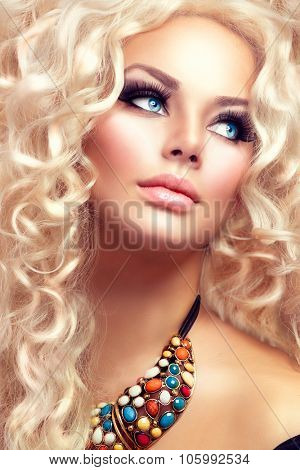 Beauty Girl With Healthy Long Curly Hair. Blonde Woman Portrait with blue eyes. Blond Wavy permed Hair and bright makeup, vivid make-up, smoky eyes and false eyelashes. Holiday make up. Perfect skin