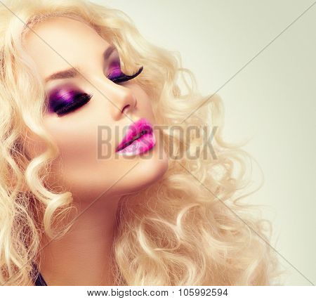 Beauty Girl With Healthy Long Curly Hair. Blonde Woman Portrait. Blond Wavy Hair and bright makeup, vivid make-up, purple lips, smoky eyes and false eyelashes. Holiday make up. Perfect skin