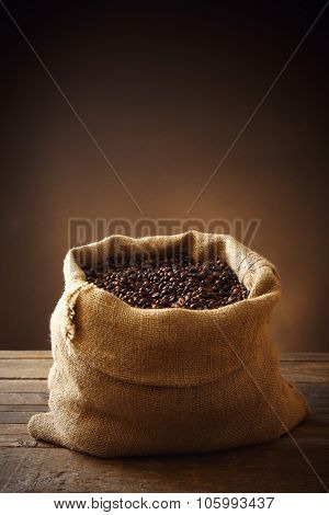 Sac with roasted coffee beans on wooden table in front of dark background