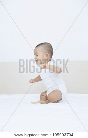 Cute Chinese baby boy playing in bed