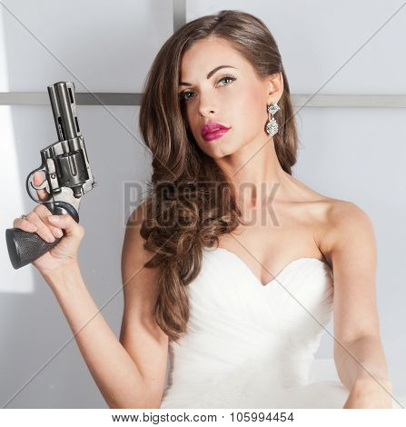 beautiful girl in a wedding dress with a gun