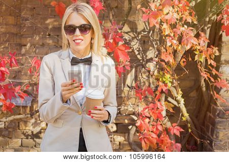 Modern female with smartphone and coffee cup in her hand