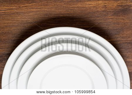 Empty white plates on wooden table