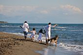 image of dog clothes  - happy young family in white clothing have fun and play with dog on vacation on a beautiful beach - JPG