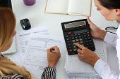 Постер, плакат: Two Female Accountants Counting On Calculator